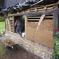 Refection d'un pignon en colombages (bois anciens, silex taillés sur place, maçonnés en terre chaux, et torchis